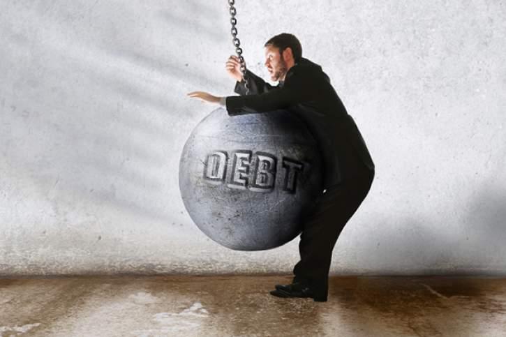 Big pile of debt tilting a person