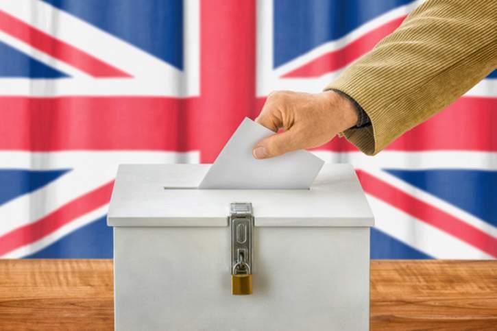 Wahlzettel wird in britische Wahlurne geworfen