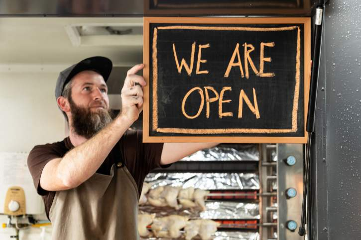 A business owner sticking a label at the front door of shop with the words, 'we are open'.