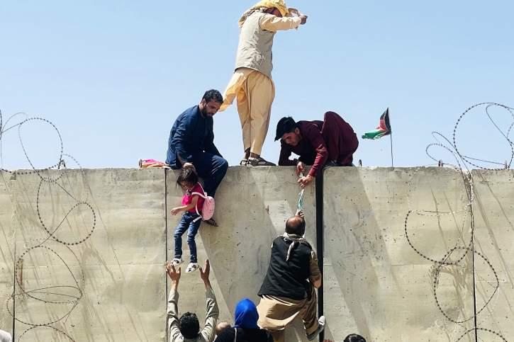 Φωτογραφία Αφγανών που σκαρφαλώνουν έναν τοίχο