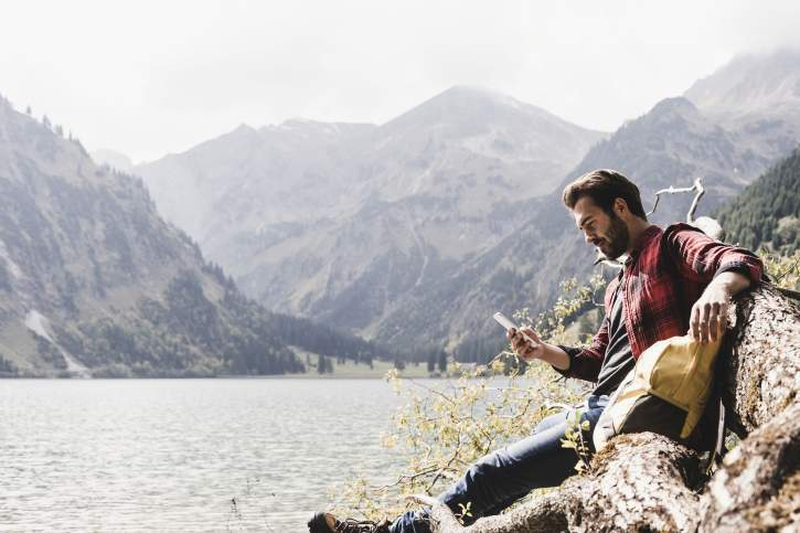 Austria, Tyrol, Alps, tourist hiker relaxing on tree trunk at mountain lake checking cell phone
