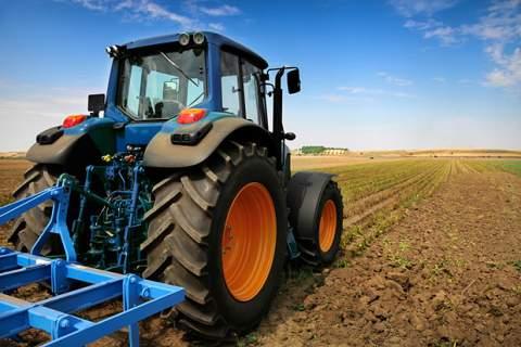 Un trattore in primo piano sul campo appena arato