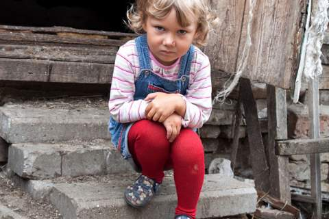 Photo of child sitting on steps of rundown home
