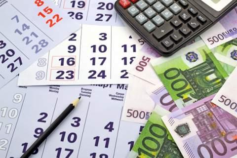 Money and calculator on month calendar