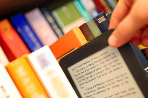 Hand Choosing an E-Book vs. Paper Books from a Bookshelf
