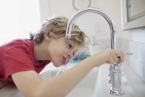 Boy drinking water from bathroom faucet