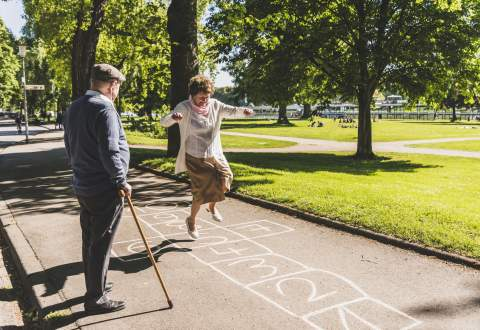 Senior woman playing hopscotch while husband watching her