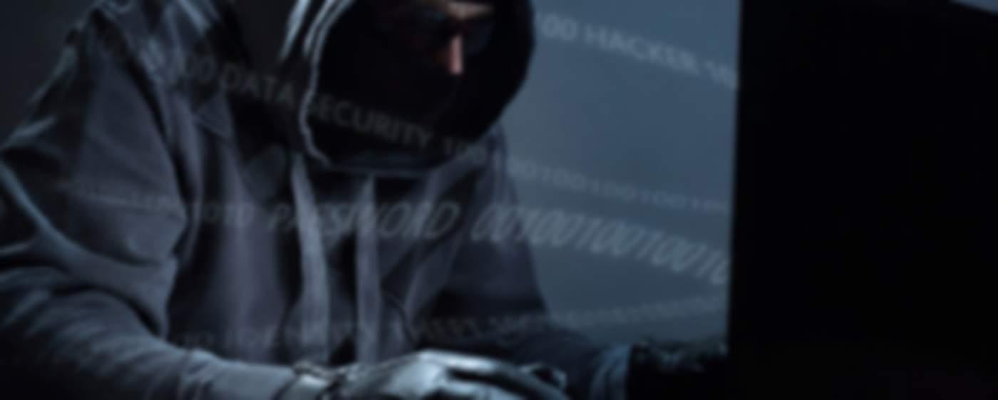 Hooded hacker steeling data from a laptop