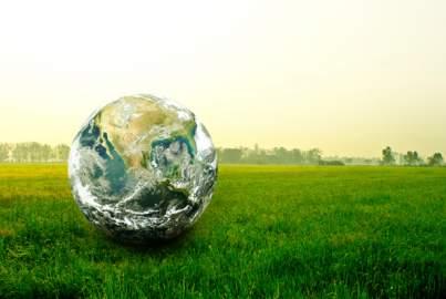 A giant glass globe sits on a field