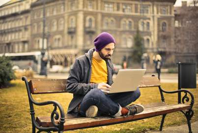 A young man sitting on a bench and working on a laptop