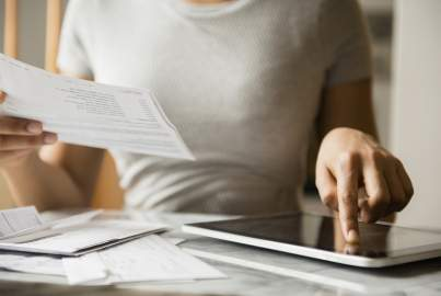A woman compares information on paper bank statements to what is on a tablet screen
